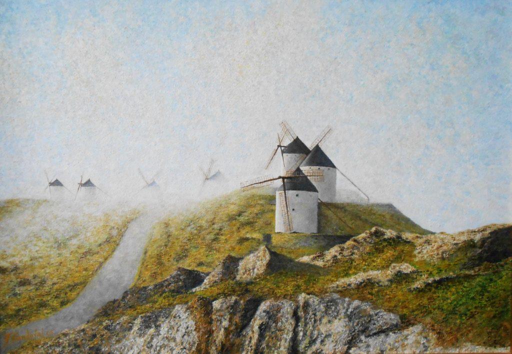 Molinos de Consuegra envueltos en la niebla otoñal, a la salida de la luz del sol incidiendo en los mismos y en las praderas que rodean dicho lugar.